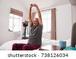 Small photo of Senior Man Waking Up And Stretching In Bedroom