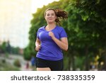 overweight young woman jogging... | Shutterstock . vector #738335359