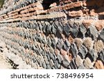 Small photo of Perimeter wall of a house of ancient Rome with the layout of the brickwork that follows the technique of Opus Reticolatum