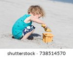 A Young Boy Is Building A Sand...