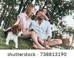 Small photo of Guess who! Happy young family of three with dog smiling while sitting on grass in park