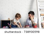 Small photo of Crayons drawing family, father looks how son draws. Development of motor skills and thinking in children garden, teacher and pedagogy, art therapy. Small artist paints with felt-tip pens and fingers
