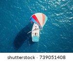 Small photo of colorful sailboats sailing at sea - rainbow baloon sail - aerial shot