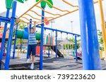 Small photo of Happy Young asian boy hang the yellow bar by his hand to exercise at out door playground under the strong sunlight in summer time.