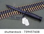 Small photo of bayonet and ammunition belt with dog tags on US NAVY uniform background