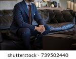 male model in a suit sitting... | Shutterstock . vector #739502440