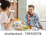 Small photo of Portrait of dark skinned man has beard and mustache calls his friend as wants to invite him for lunch, looks on his wife with love. Family couple have breakfast at kichen. Everyday life concept