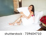 indian woman sitting on a bed... | Shutterstock . vector #739604710