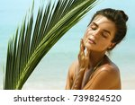 Small photo of Portrait of beautiful woman with shadows of palm leaf on her face
