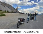 Small photo of Italy Piedmont Alps circa June 2015 Group of vintage motorbike rider layover front view in mountain landscape with cloudy sky