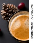 Small photo of Glass of americano espresso fresh made dark black strong coffee on wooden board table, thick froth foam in cafe, red berries and pine cones, autumn morning hot drink caffeine, copy space for text