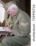 Small photo of British home guard Sergeant sat at wooden desk in the field writing records
