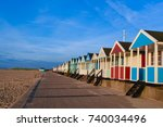 colourful beach huts by sandy...