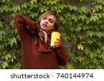 Small photo of Portrait of young attractive woman posing, holding yellow cup of coffee near the wall with green leaves of grope.
