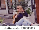 blond girl sitting in cafe with ... | Shutterstock . vector #740308099