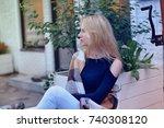 blond girl sitting in cafe | Shutterstock . vector #740308120