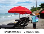 Small photo of Cambodia Sihanoukville. a woman in a blue shirt walks along the beach, along the sea, past sun loungers (chaise longue) and an umbrella from the sun. seller of fried shrimp and street food.