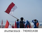 Small photo of A son uncase an Indonesian flag