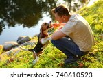 Stock photo man sit on squat on haunches at green bank of river play with young beagle dog owner tease doggy 740610523