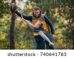 Small photo of happy father and son playing with rugby ball in forest