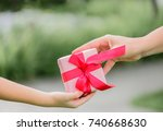 mother hand giving a gift box...   Shutterstock . vector #740668630