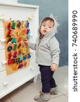 Small photo of Child toddler boy playing with toys at home. Little boy standing near Russian alphabet