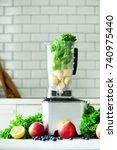 woman blending lettuce leaves ... | Shutterstock . vector #740975440