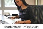 female office worker writing... | Shutterstock . vector #741019084