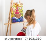 Small photo of A little cute little girl, four years old, sits behind an easel and paints a watercolor ship flying through the sea. The child plays and develops. A kid at home. Ethical education and training.