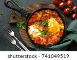 Small photo of Shakshuka - eggs in tomato sauce in a skillet over dark green slate,stone or concrete background.Top view .