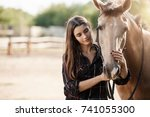 Stock photo young female assistant farm manager caring about a horse 741055300