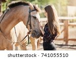 Stock photo young female horse farm manager caring and petting young stallion dream career taking care about 741055510