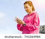 sporty woman with earphones on... | Shutterstock . vector #741064984