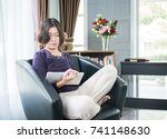 Small photo of Close up beautiful young asian woman short hair use mobile phone in living room at home