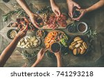 Small photo of Flat-lay of friends hands eating and drinking together. Top view of people having party, gathering, celebrating together at vintage wooden rustic table set with different wine snacks and fingerfoods