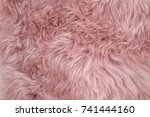 Pink sheepskin rug background. Wool texture. Close up sheep fur