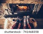 feet in woollen socks by the... | Shutterstock . vector #741468358