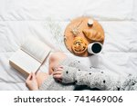 woman sitting in bed reading a... | Shutterstock . vector #741469006