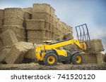 Yellow Tractor Stacks Bales Of...