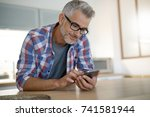 middle aged man at home using... | Shutterstock . vector #741581944