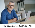 middle aged man working from... | Shutterstock . vector #741584158