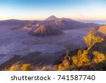 Small photo of Bromo Tengger Semeru National park when sunrise in the morning. The sky turn in to purple with high velocity wind blows aflutter grass in foreground.