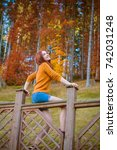 Small photo of A woman is resting in a beautiful autumn forest dressed in a yellow knitted sweater and denim shorts. The concept of rest in the countryside and relaxation in nature
