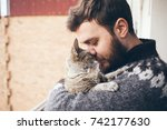 Stock photo cat and man portrait of happy cat with close eyes and young man people playing with the kitten 742177630
