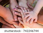 a group of hands piled together ... | Shutterstock . vector #742246744