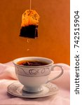 Small photo of Tea bag with tea drops and small splash on a cup of tea