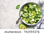 Small photo of Avocado salad with broccoli,cucumber and boiled eggs in a white vintage bowl over light slate,stone or concrete background.Top view.