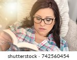 pretty young woman reading a... | Shutterstock . vector #742560454