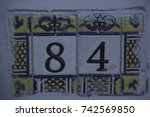 Small photo of Number eighty-four in antique tile, on the wall.
