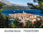 Small photo of The old town of Korcula jutting out into the turquoise Adriatic on its own peninsula captured between a gap in trees on the hillside.